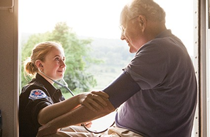 Female medical technician attends elderly man