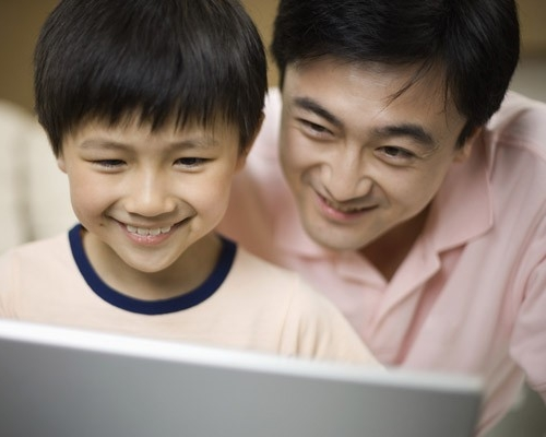 Father and son looking at laptop computer