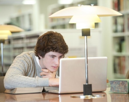 Male student using laptop computer in library