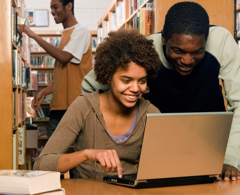 Students searching for books in library