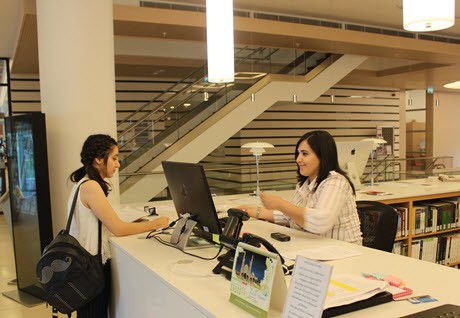 Student and librarian at ADA University Library's circulation desk