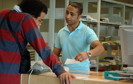 Male student checking out materials