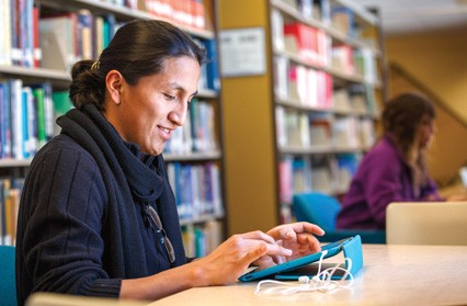 Person uses tablet computer in a library