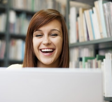Happy person using computer in library