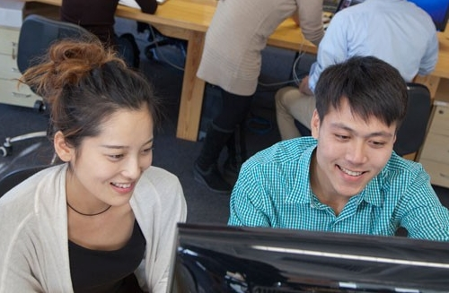 Male and female students looking at computer